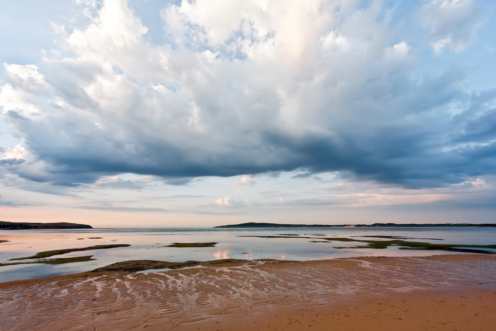 Beautiful clouds over shallow waters and sandy beach. Minimalist