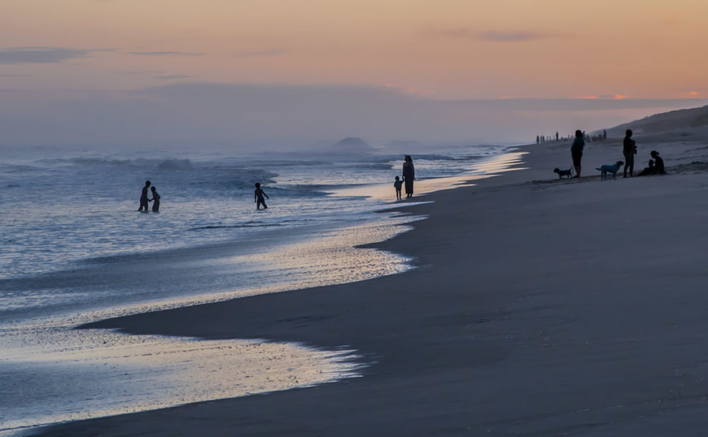 People relaxing on the beach at sunset
