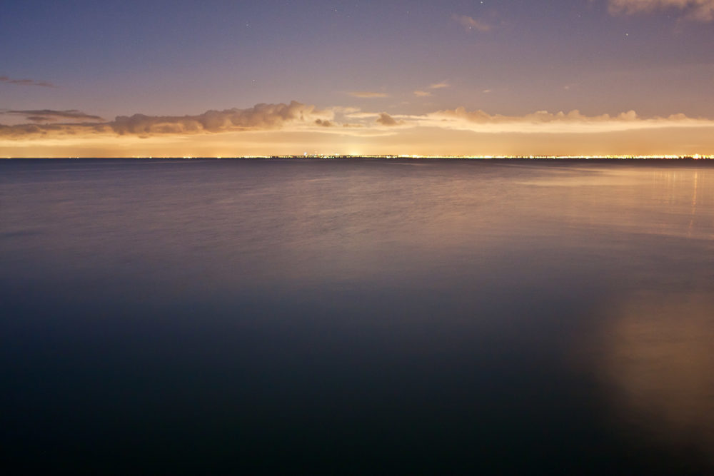 Smooth water surface with distant Melbourne lights