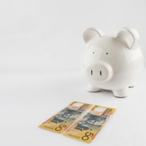 Piggy bank standing near two Australian 50 dollar bills isolated on white