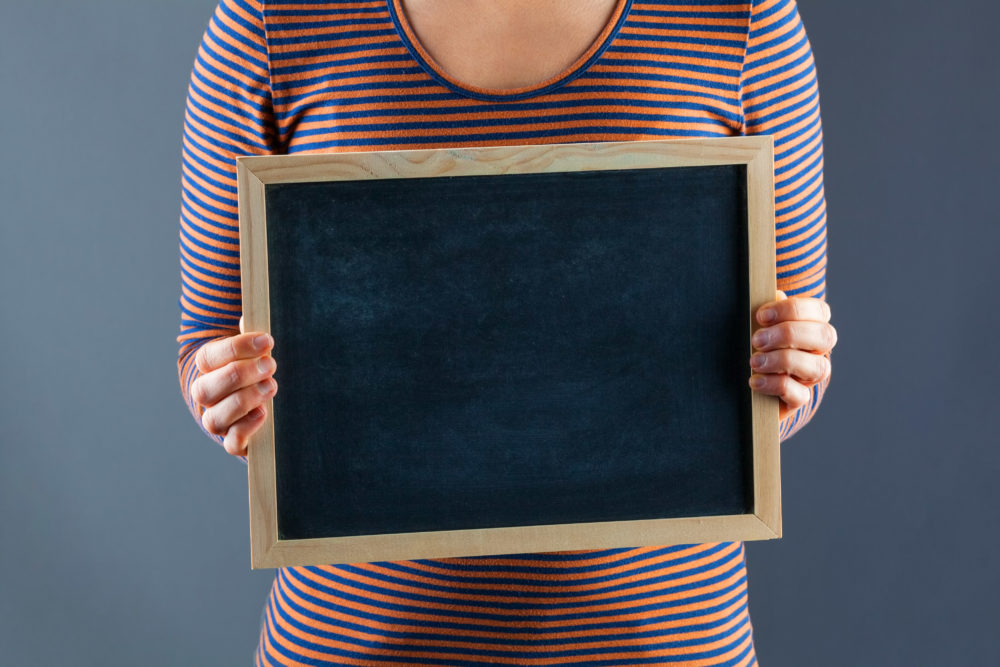 Female hands holding small black chalkboard.