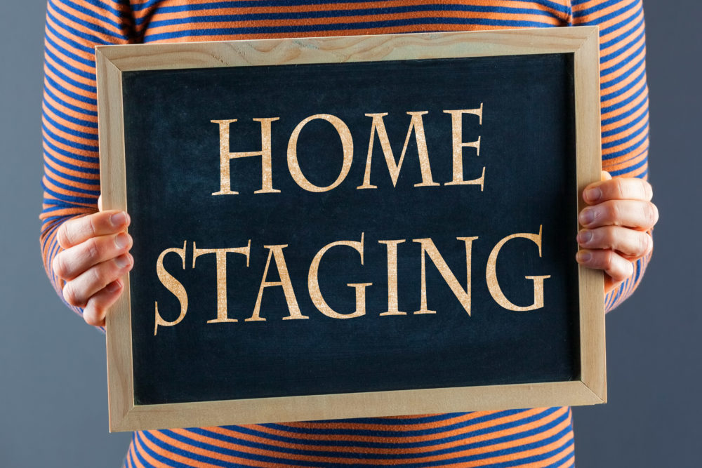 Female hands holding small black chalkboard in front of the body closeup with words Home Staging. On gray background with copy space