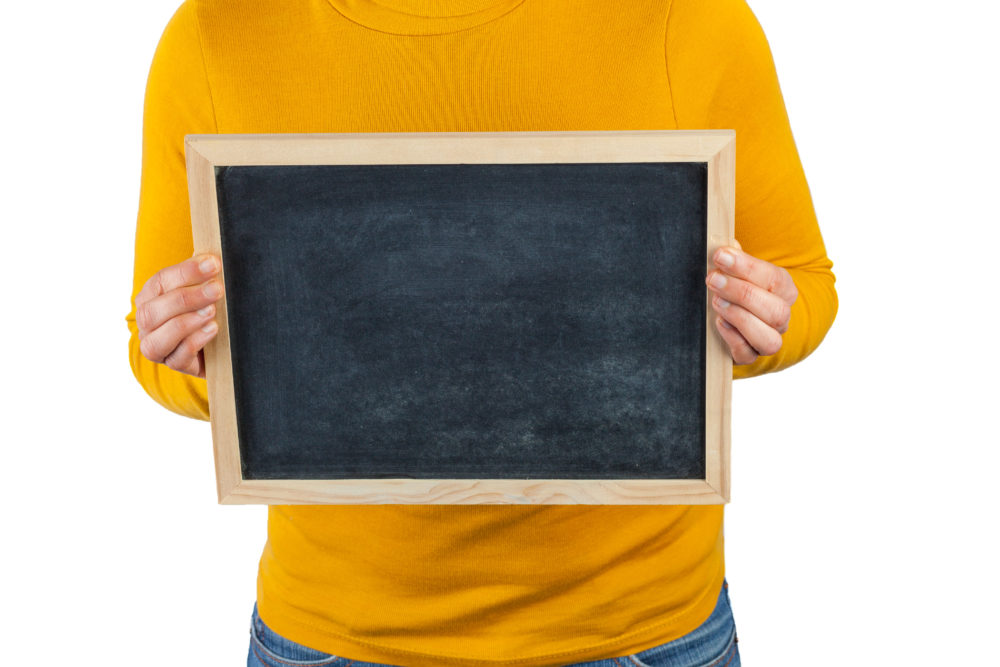 Female hands holding small black chalkboard in front of the body