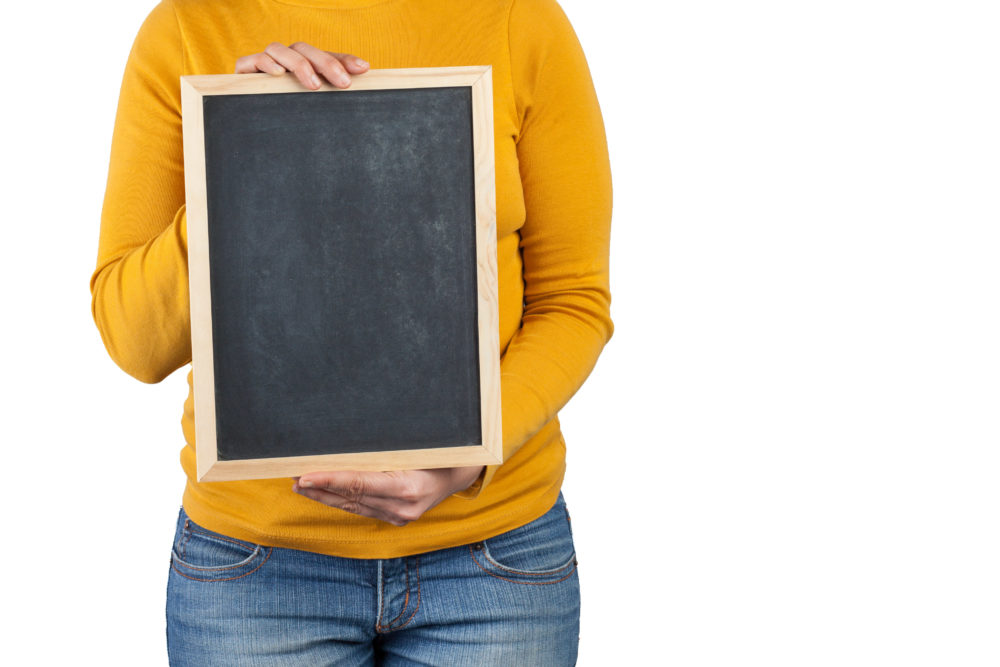Female hands holding small black chalkboard vertically in front of the body closeup isolated on white background with copy space
