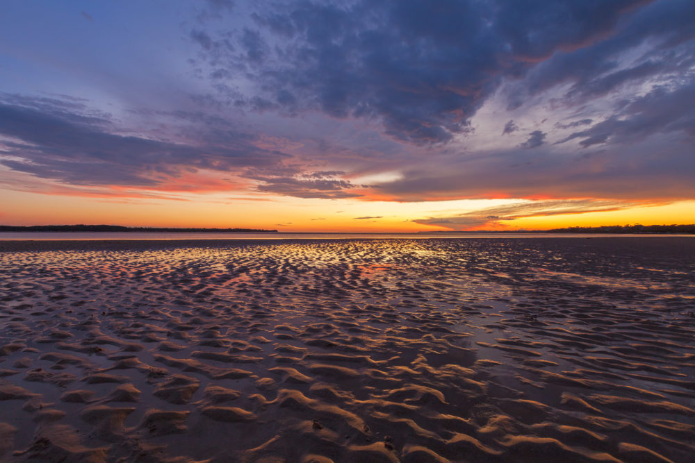 Beautiful glowing sunset reflections in sand ripples