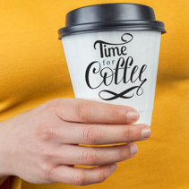Female hand holding a disposable white coffee cup with Time For Coffee hand lettering