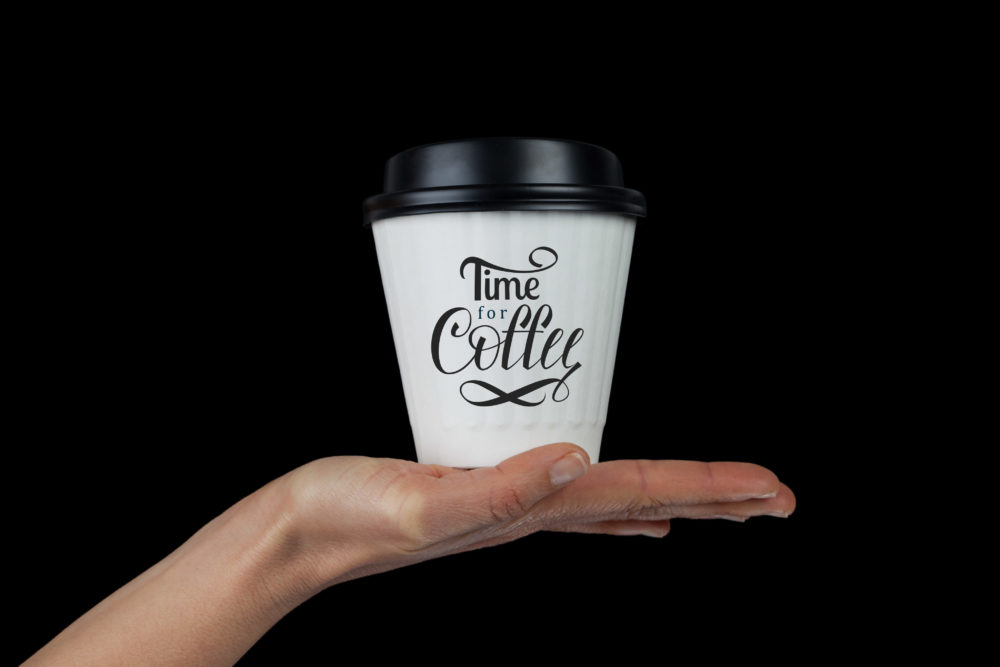 Female hand with white coffee cup on palm isolated on black with Time For Coffee hand lettering