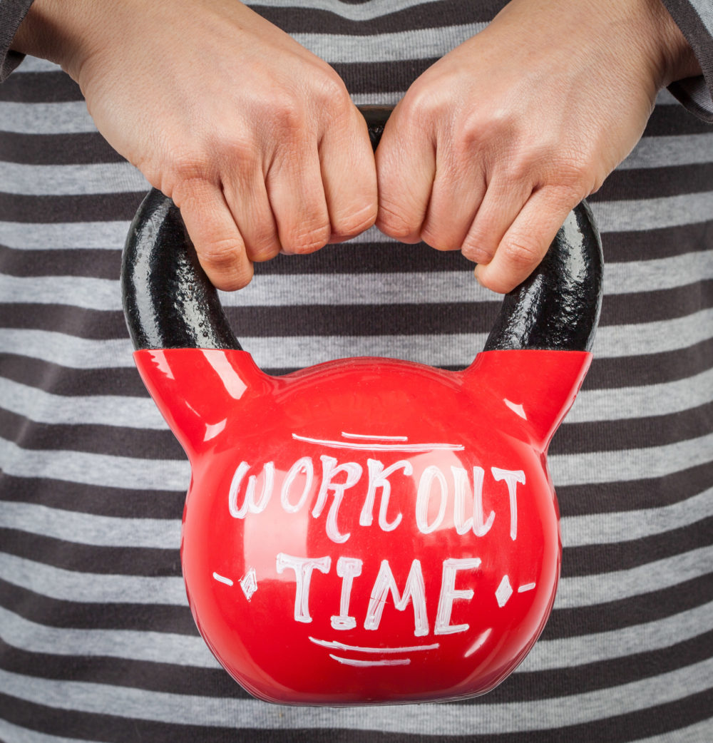 Female hands holding red kettlebell with workout time lettering closeup. Healthy lifestyle concept
