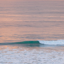 Breaking turquoise ocean wave at sunset.