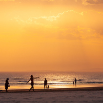People and dogs silhouettes on ocean beach at orange sunset in Australia. One person is dancing