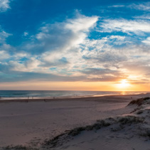 Beautiful panorama of people silhouettes walking on ocean shore at sunset in Australia