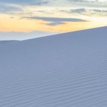 Sand ripples on white dune at sunset
