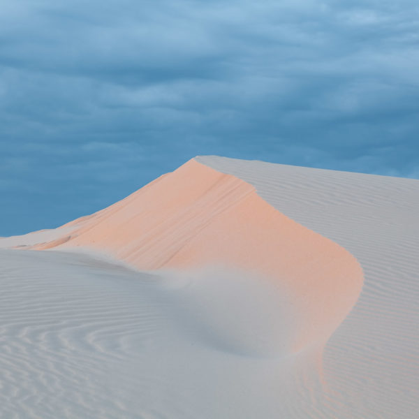 Beautiful white sand dune under cloudy sunset skies. Anna Bay, New South Wales, Australia