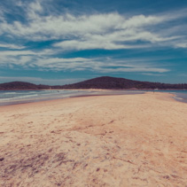 People walking on Fingal sand spit near Fingal Island at Fingal Bay, New South Wales, Australia