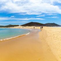 People walking on the beach towards Fingal Island at Fingal Bay, NSW, Australia