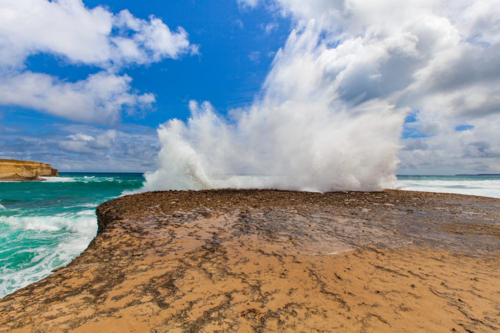 Big wave breaks on a rock with explosion like splashes