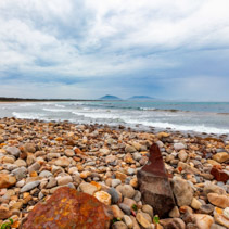 Vivid orange pebbles on ocean beach at Crowdy Head, NSW, Australia