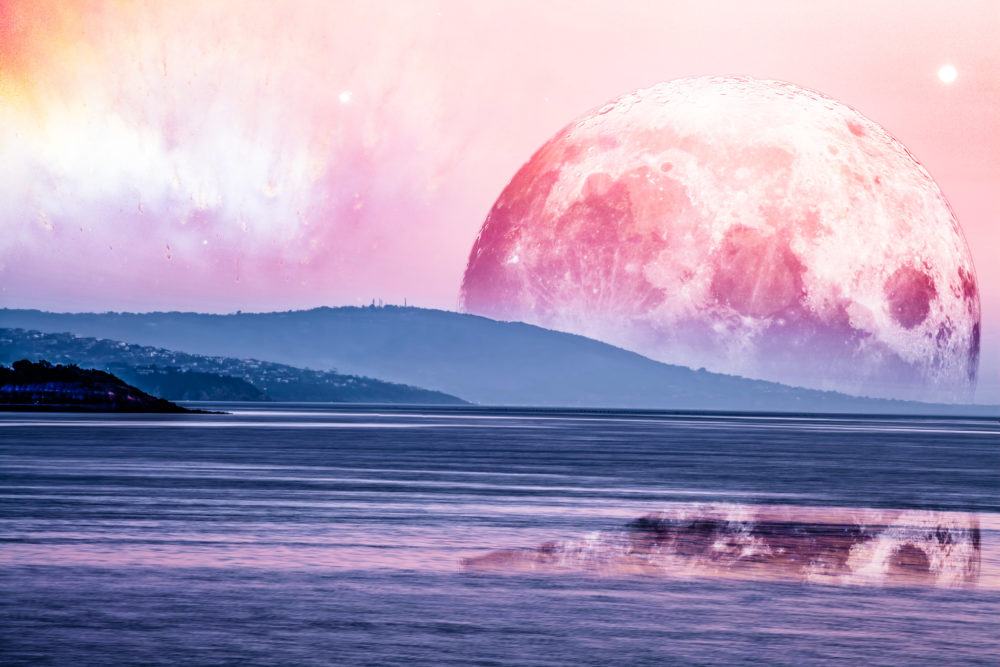 Landscape of an alien planet - huge pink moon reflects in calm ocean water. Elements of this image are furnished by NASA