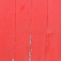 Red paint peeling from wood background