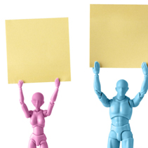 Male and female figurines closeup holding up yellow square pieces of paper above their heads isolated on white with copy space