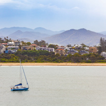 Sailboat sailing at Coffs Harbour with luxury homes and mountains in the background