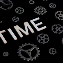 Concept of time depicted with cog wheels, watches and letters isolated on black background