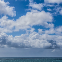 Fluffy clouds and calm ocean water - deep blue colors