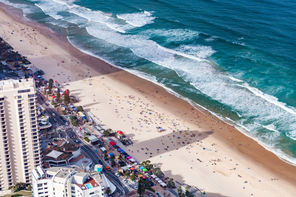 Aerial view of people on Surfers Paradise ocean beach in Queensland, Australia