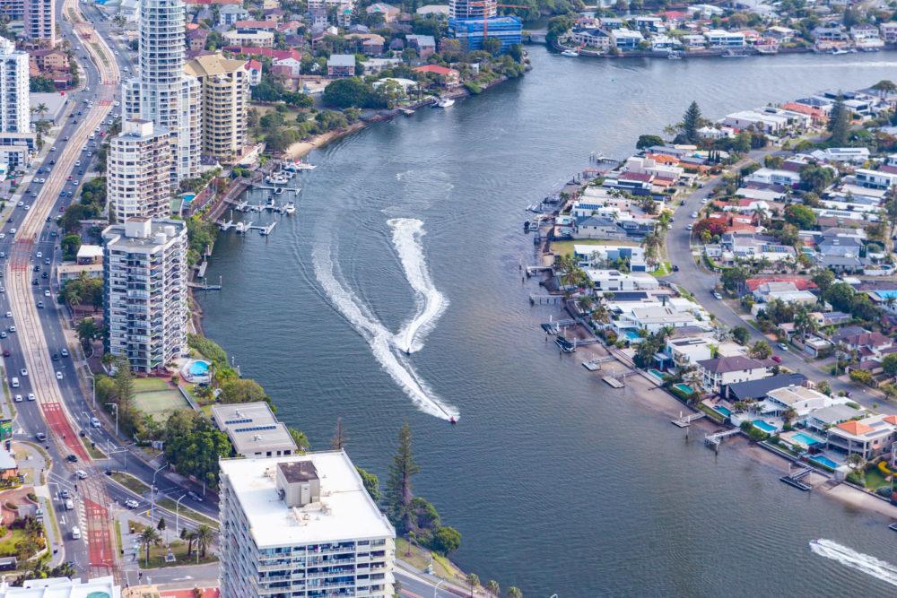 Jet ski speeding on Nerang River among luxury real estate of Gold Coast city