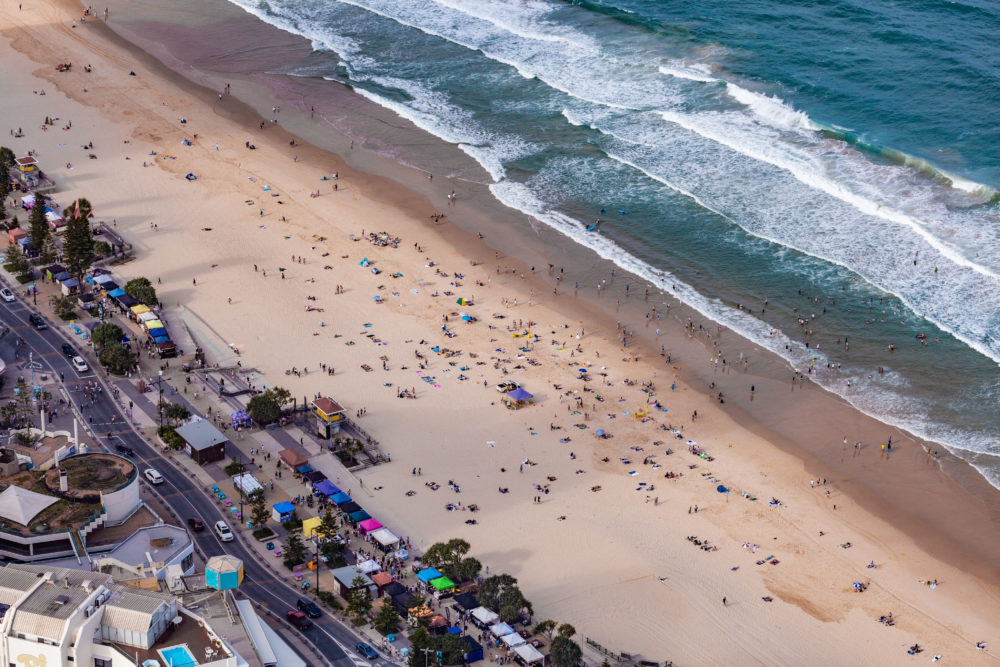 Aerial view of people on Surfers Paradise ocean beach next to the market