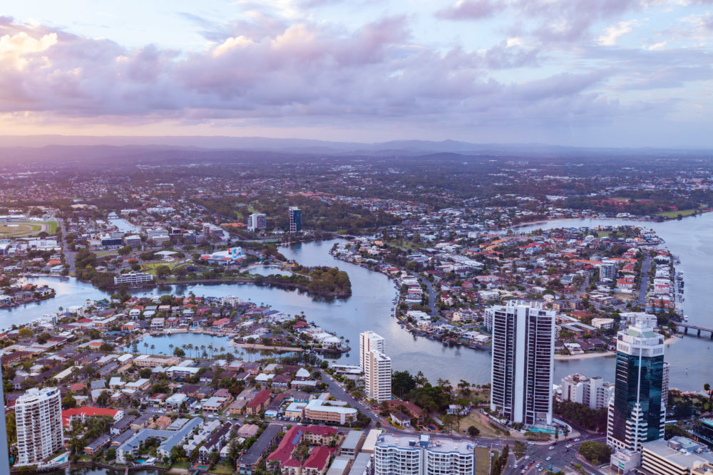 Aerial landscape of Gold Coast luxury real estate and Nerang river at sunset