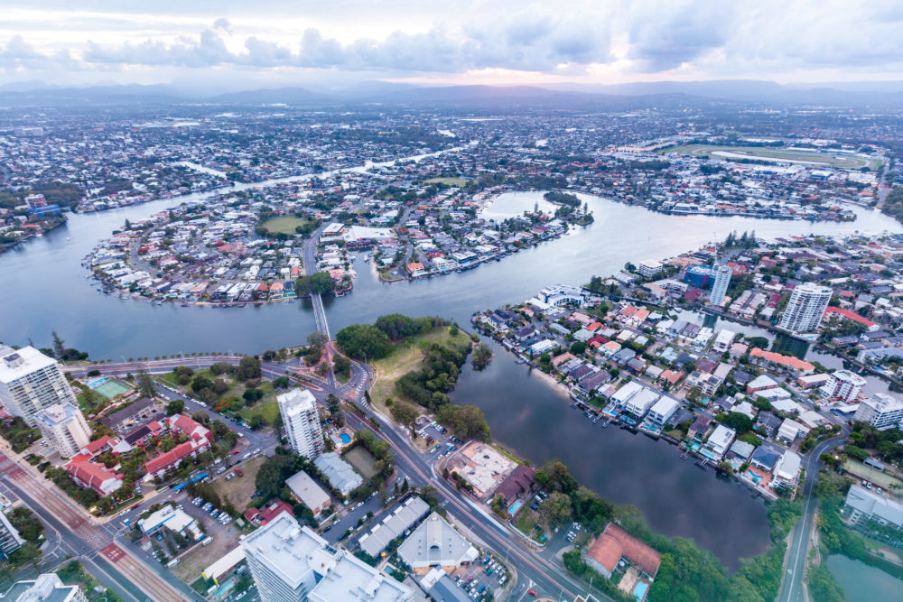 Nerang river flowing around luxury real estate on the Gold Coast at sunset - aerial view