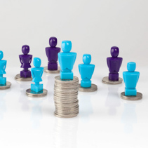 Wage gap and unequal money distribution concept shown with male and female figurines standing on coin piles