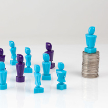 Leadership and corporate structure concept portrayed with male and female figurines and coins.