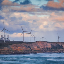 Wind turbines standing on rugged cliff above ocean in Australia at sunset