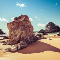 Beautiful rock formation on ocean beach on bright sunny day