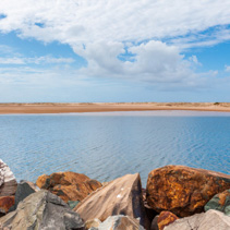 Breakwater stones over calm waters and stretch of sand under blue skies - minimalist landscape
