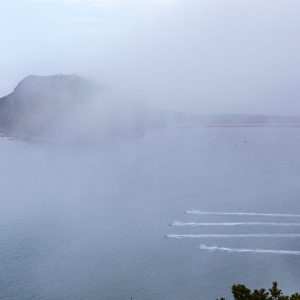 Four jet skis racing acros the water near Barrenjoey Lighthouse in low visibility clouds. Ku-ring-gai Chase, Sydney, Australia