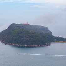 Barrenjoey Lighthouse and smal boat leaving water trail