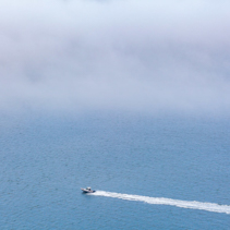 Small boat sailing across the ocean leaving water trail under low clouds with copy space