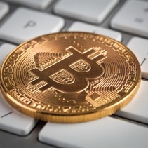Golden Bitcoin on white keyboard closeup - cryptocurrency concept
