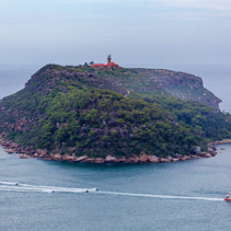 Passenger ferry and jet skis sailing around Barrenjoey Head Lighthouse in Sydney, Australia