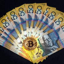 Golden Bitcoin glowing on top of Australian 50 dollar banknotes on black background