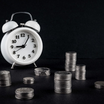 Vintage alarm clock showing 9 o'clock and coin towers on black background. Time is money business concept