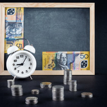 Vintage alarm clock showing 9 o'clock, coin towers and 50 Australian dollars bills on empty chalkboard. Time is money business concept