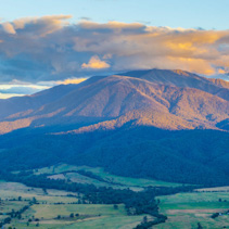 Aerial view of orange sunset light on beautiful mountain in Australian Alps