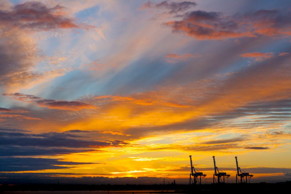 Port cranes silhouettes in glowing sunset