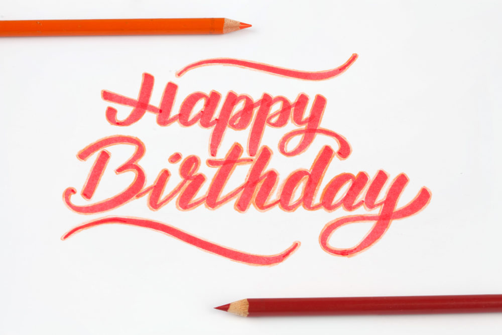 Happy birthday lettering on white background with pencils
