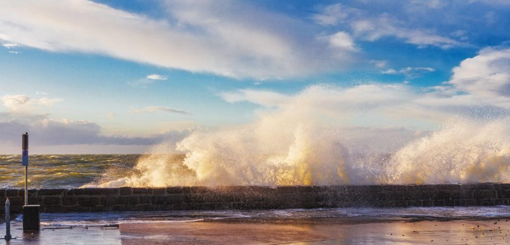Big waves crushing on pier at sunset