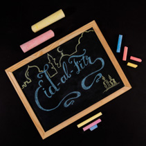 Eid al Fitr greeting hand written with colorful chalk on blackboard - top view